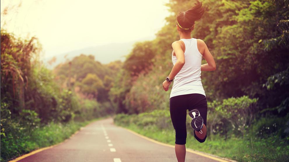 mujer corriendo con pulsera deportiva