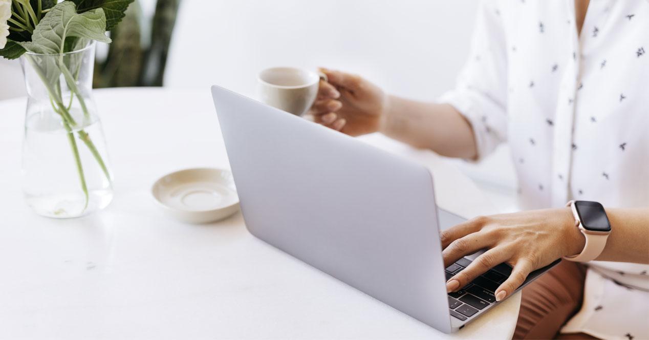 Uso de ordenador portátil con café en la mano