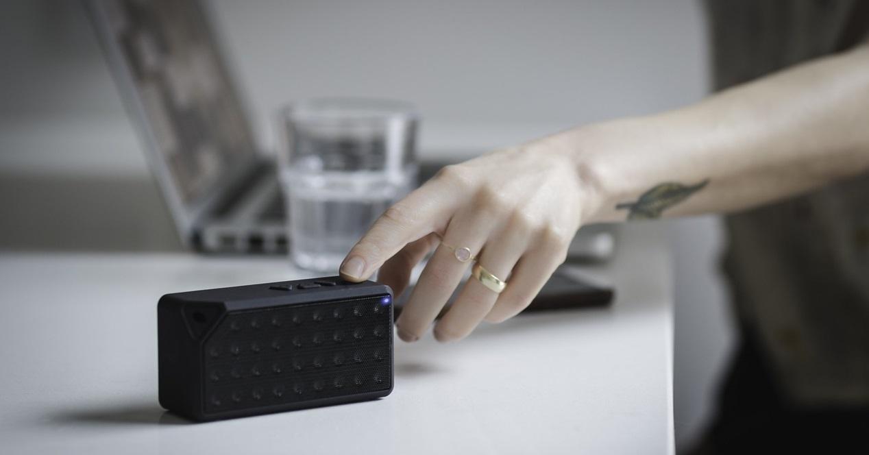 altavoz bluetooth y mano tocando